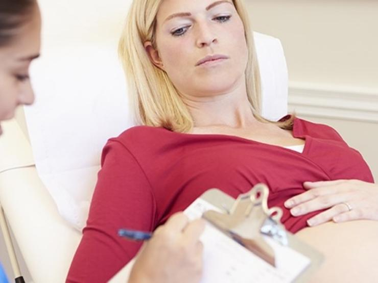 Pregnant woman on hospital bed, with her pregnant belly showing, with midwife writing notes