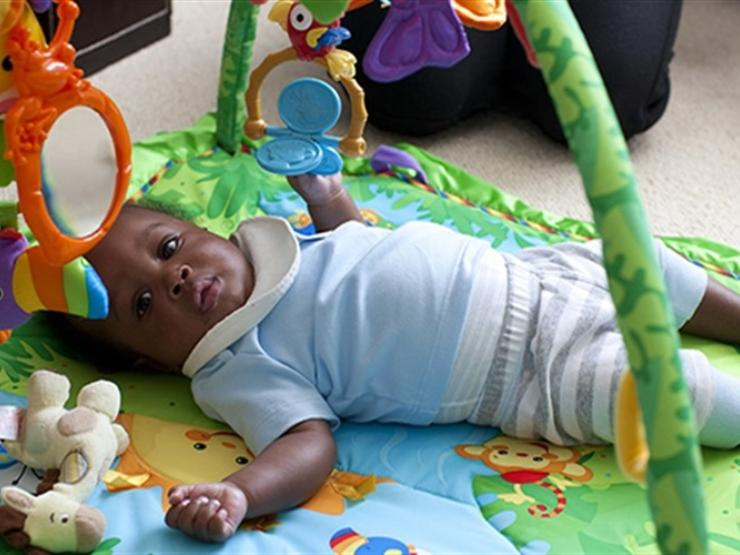 Baby lying on play mat at home looking towards the camera