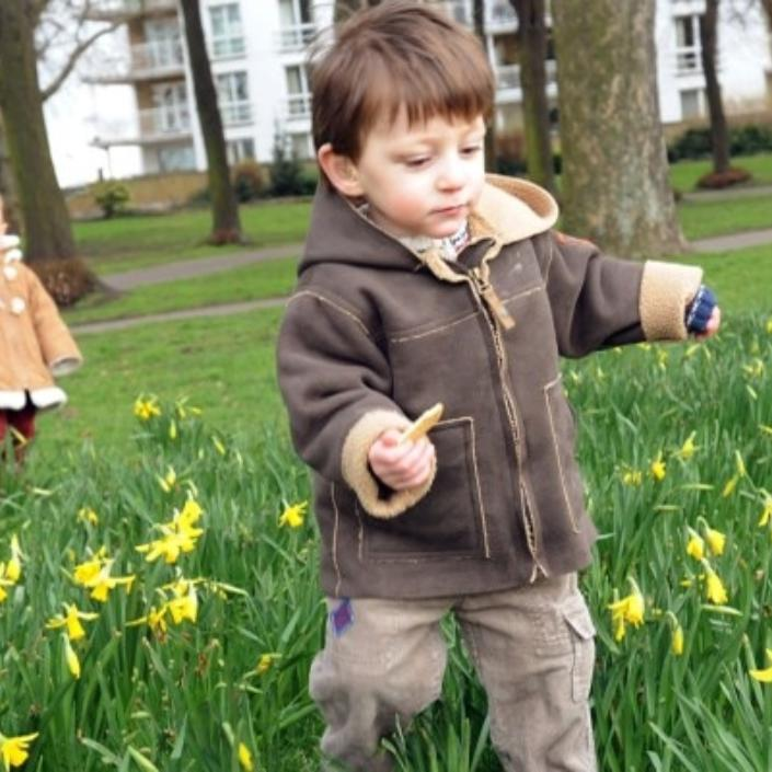 Little boy in foreground and little girl in background about the age of toddler running through daffodils in a park