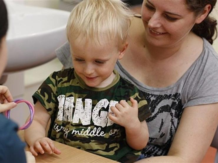 Little boy aged about 3 sitting on his mum at a table doing a task with health professional who has their back to camera