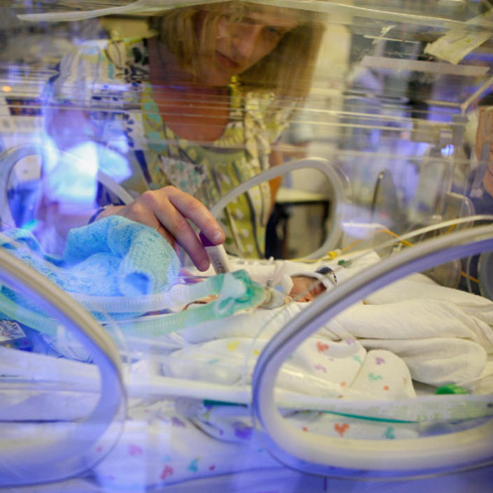 Mum holding hands with baby in incubator