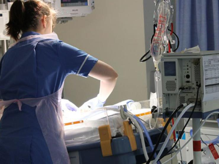 Nurse with her back to camera looking after a baby in a cot, surrounded by lots of medical equipment