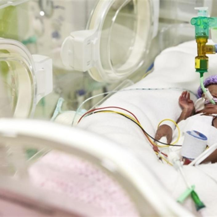 Baby in a cot in hospital on a ventilator