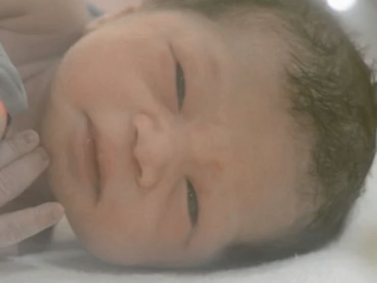 Close up on baby's face lying on side in cot - baby has dark hair and features in the video on this webpage