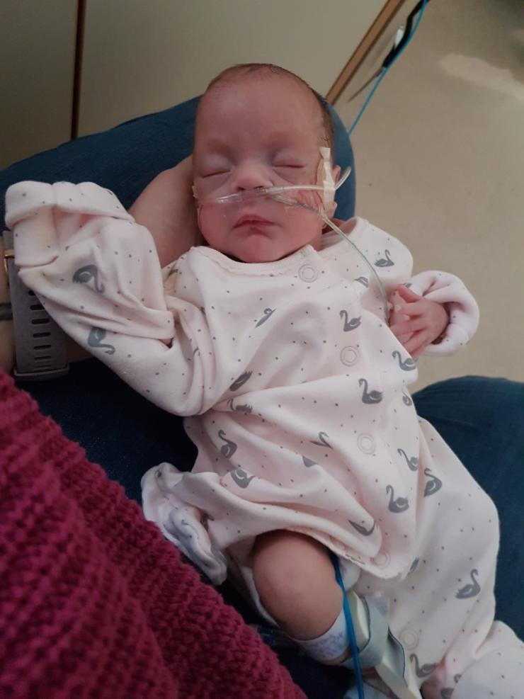 Elizabeth being held on lap in hospital