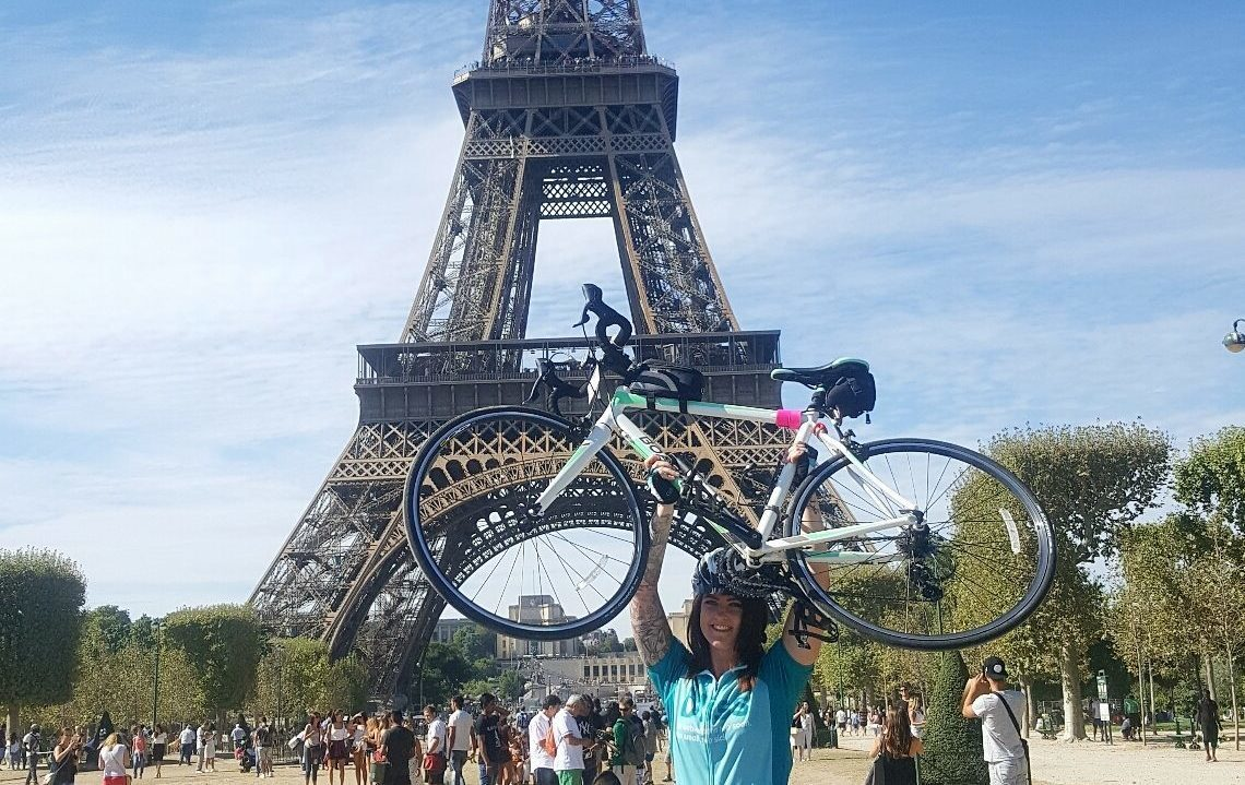 Bliss rider holding her bike above her head in front of the eiffel tower