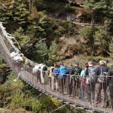 People crossing a bridge on the trek