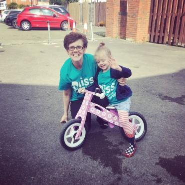 Little girl on push bike and her grandma