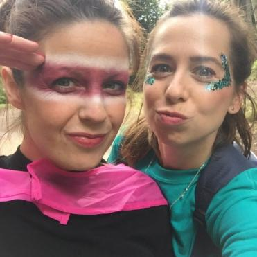 Two women dressed up in superhero outfits with face paint posing for the camera