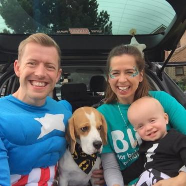 Family of mum, dad, baby and their dog with dad dressed as superhero at a Little Heroes walk