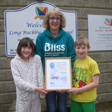 School children in pyjamas with Bliss fundraising certificate