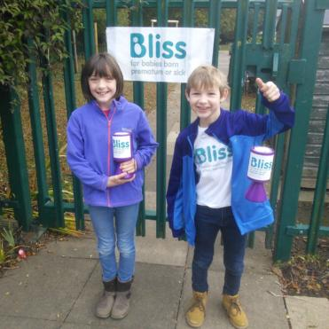 two young pupils at non school uniform day with Bliss t-shirts and collection tins