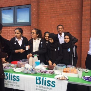Pupils holding a cake sale at School with Bliss branding