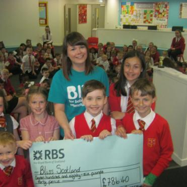 Bliss representative collecting cheque from school children