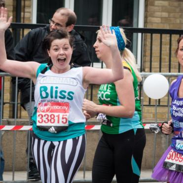 A lady waving at the camera whilst running in the london marathon