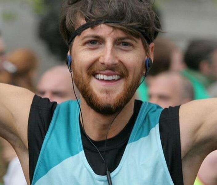 Head shot of man running celebrating with arms in the air at an event wearing a Bliss running vest