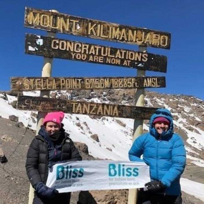 2 trekkers at the summit with Bliss sign