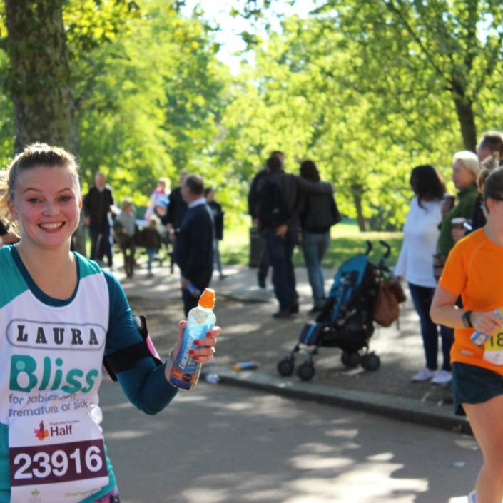 Lady running Royal Parks Half Marathon waving