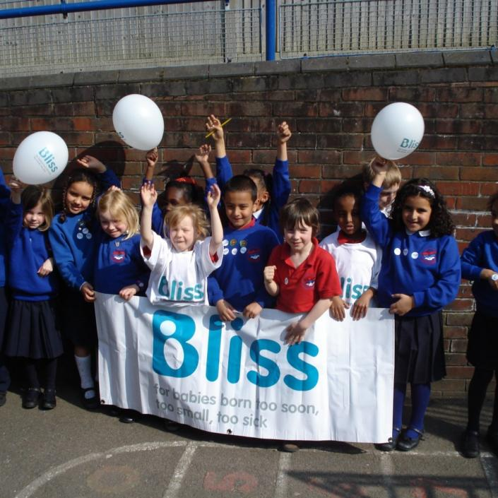 group of school children with Bliss banner and balloons