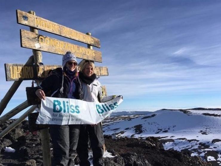 2 people at the summit of Mt Kilimanjaro
