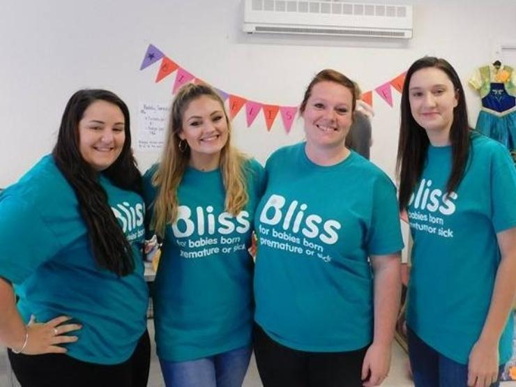 Group of 4 girls in Bliss t-shirts at an event