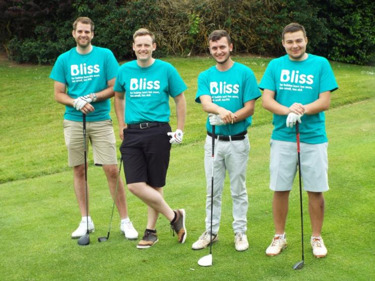 four men posing with Golf clubs wearing Bliss t-shirts