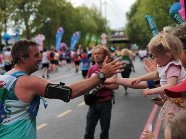 Man giving his daughter a high five as he runs along