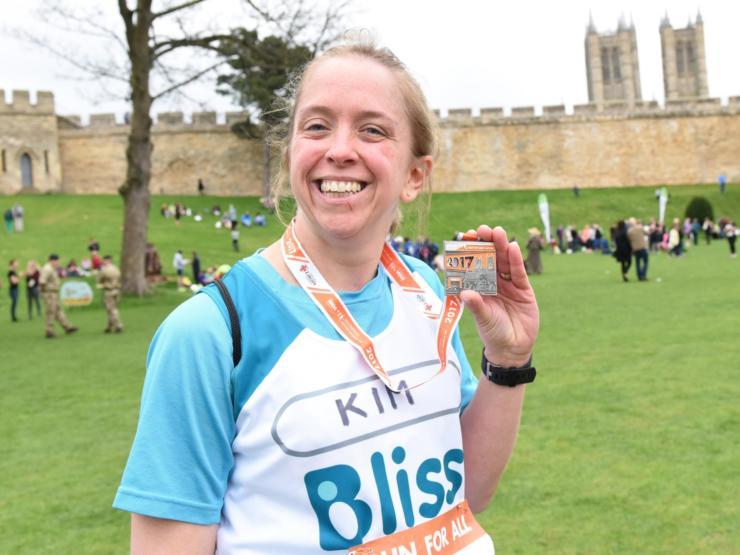 Women showing her running medal