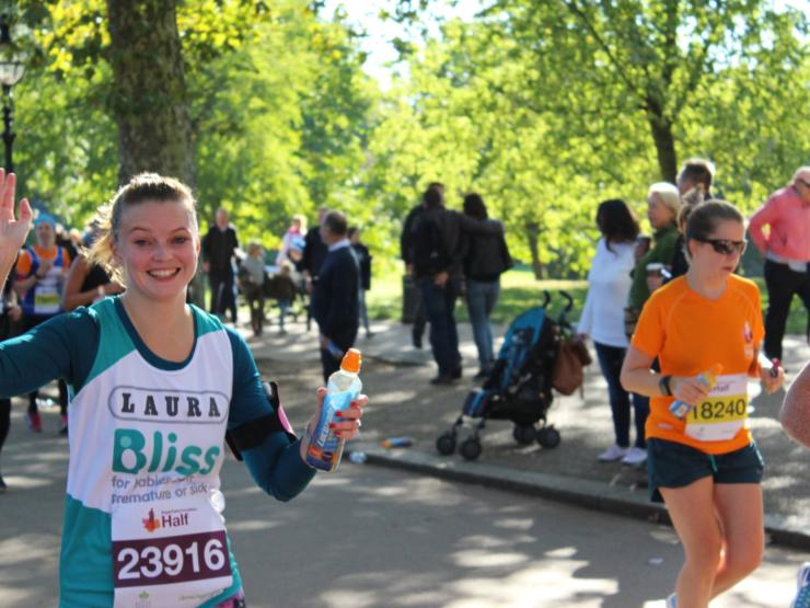 Lady running Royal Parks Half Marathon waving