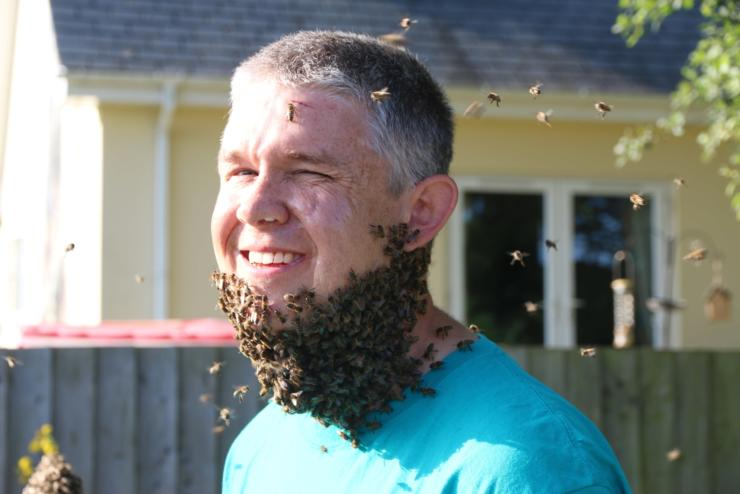 Man with bees swarming around his chin