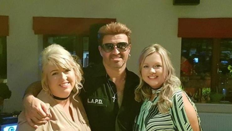 two ladies posing with a George Michael tribute singer
