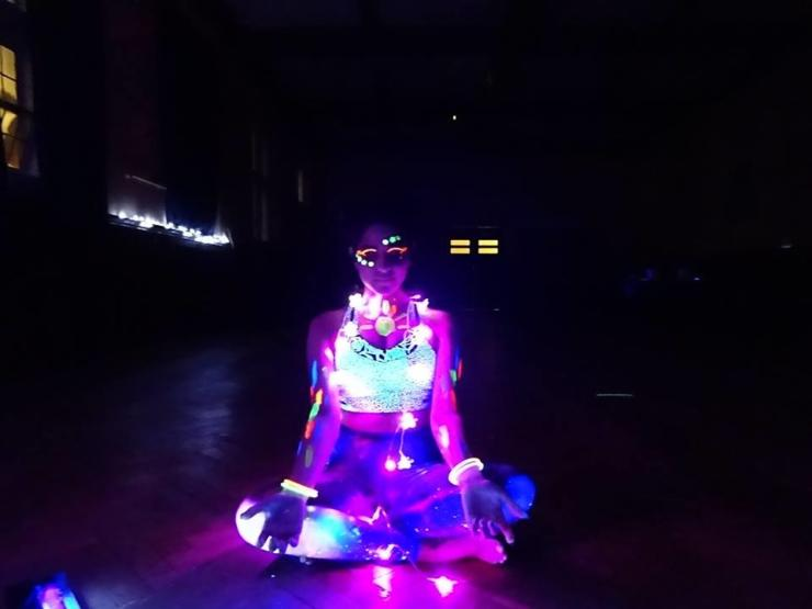 lady sitting in cross legged yoga position with lights and UV glow sticks