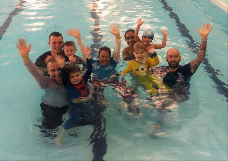 Children with their parents in a swimming pool wearing pyjamas
