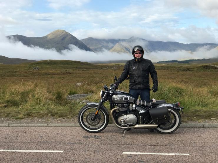 Man next to Motorbike with Mountains in background