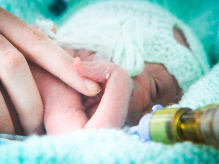 Baby holding parents finger