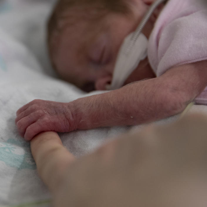 Baby lying on front asleep holding the finger of an adult