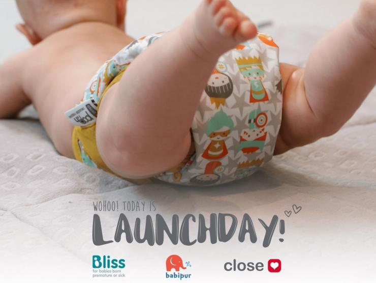 Baby wearing resuable nappy by Close Parent company, with launchday and Bliss and company logos on the image