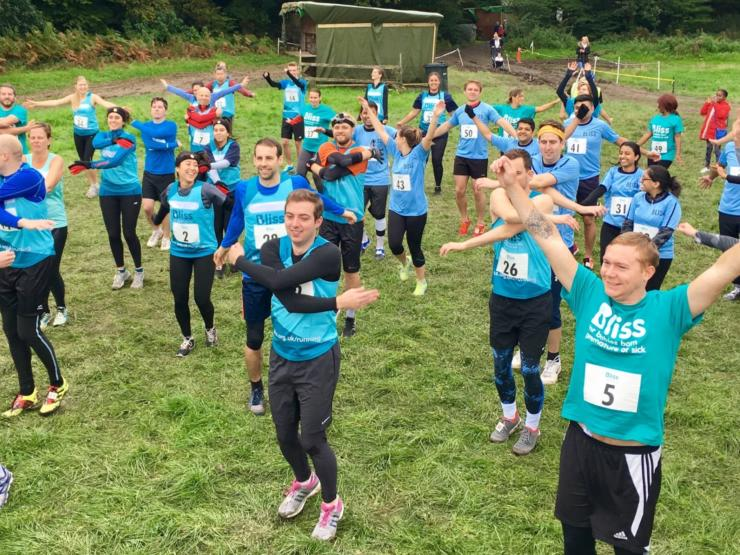People wearing Bliss t-shirts and vests warming up to take part in a mud run