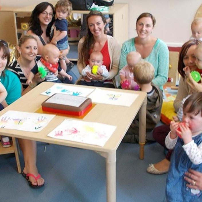 Group of mums and babies with Bliss volunteers sitting around a table in a play area