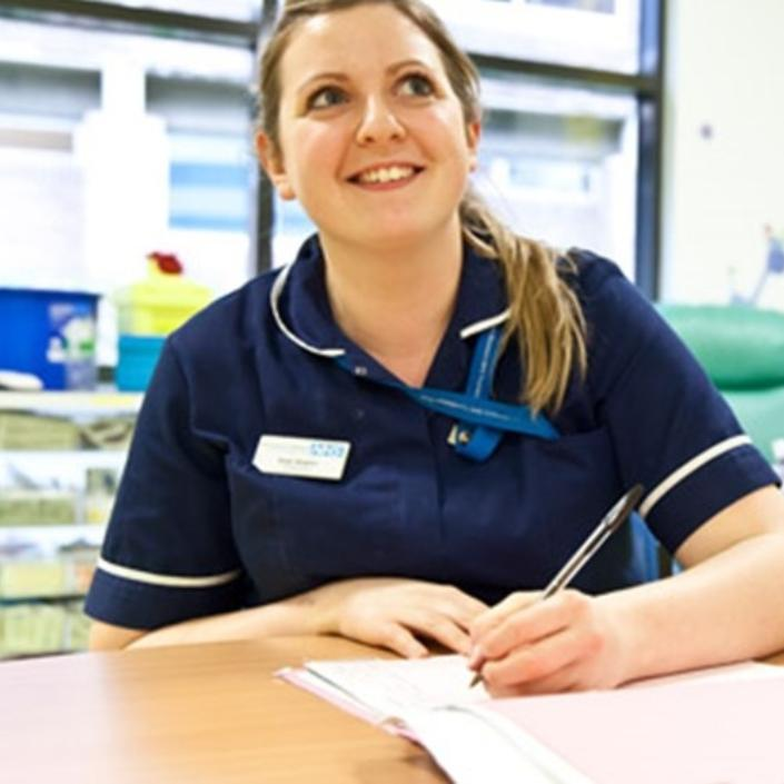 Nurse sitting at a desk with paperwork looking up and smiling