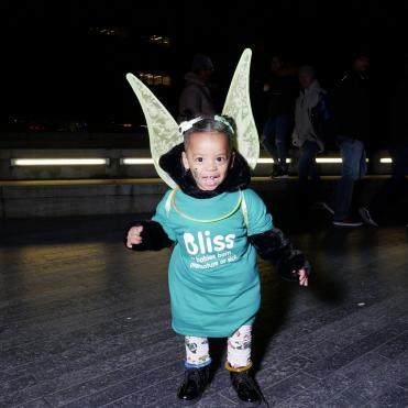 Young child wearing Bliss t-shirt, glowstick necklack and angel wings