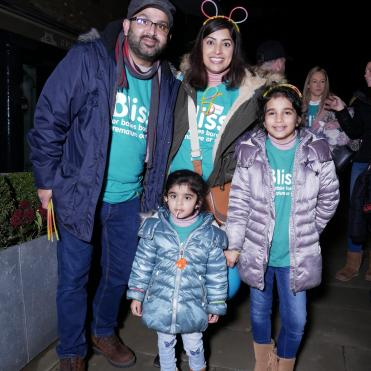 Family wearing warm coats, Bliss t-shirts and glow stick head bands and necklaces at a night time event