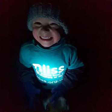 Little boy wearing beanie hat and Bliss t-shirt in dark, t-shirt lit by torchlight