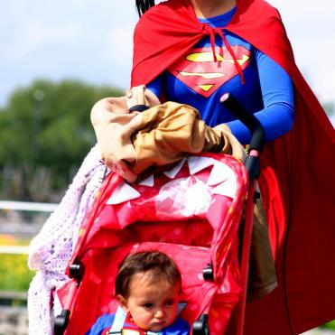 Woman in superhero costume pushing baby in same superhero costume in pushchair