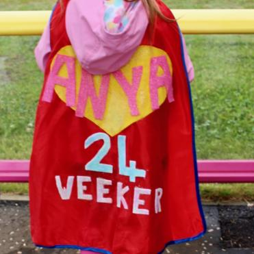 Little girl with a superhero cape that states she was born at 24 weeks gestation