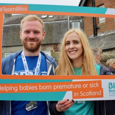 Man and woman taking picture with Bliss photo frame after completing a running event