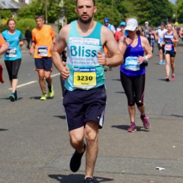Man in Bliss running vest running with other runners behind him.