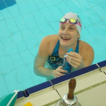 woman in an indoor swimming pool smiling