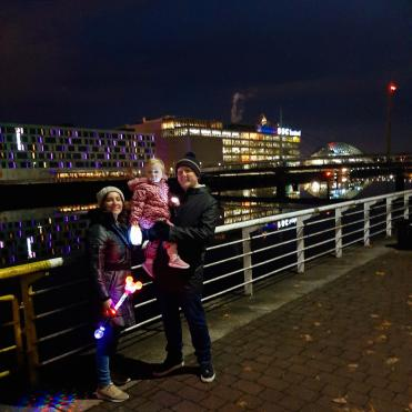 Family standing by River Clyde at night with BBC Scotland building in background