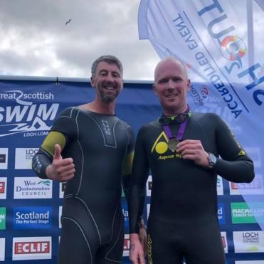 Two men in wetsuits showing their medals after doing the Great Scottish Swim